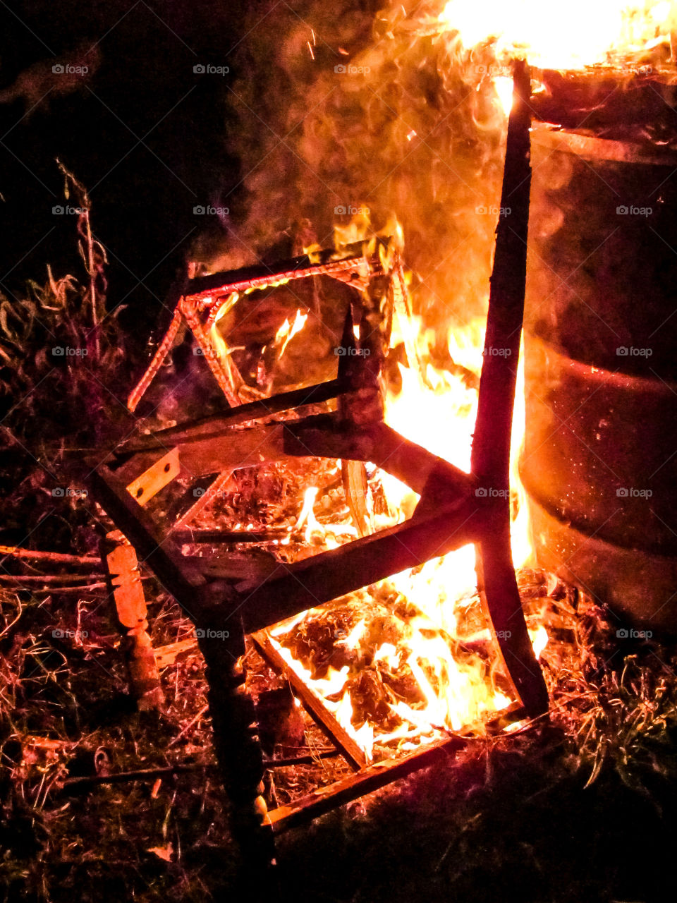 wooden chair on fire at night outdoors