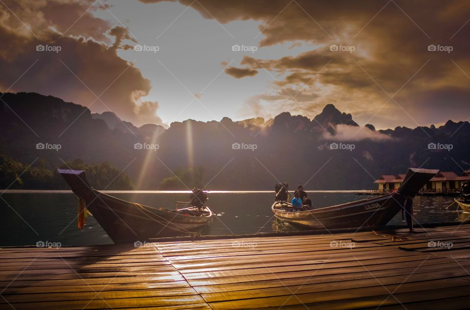 Morning in Thailand. Morning after sunrise raised up, sun rays hit the boats and wooden pier, Khao Sok national park, Thailand.