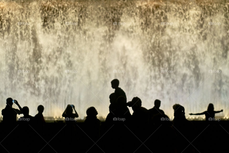 Silhouette of people in front of fountain