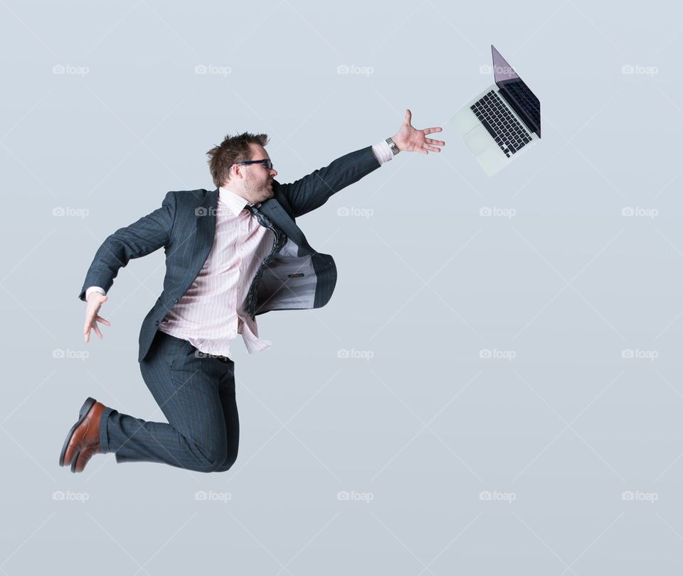 Young businessman and laptop against grey background