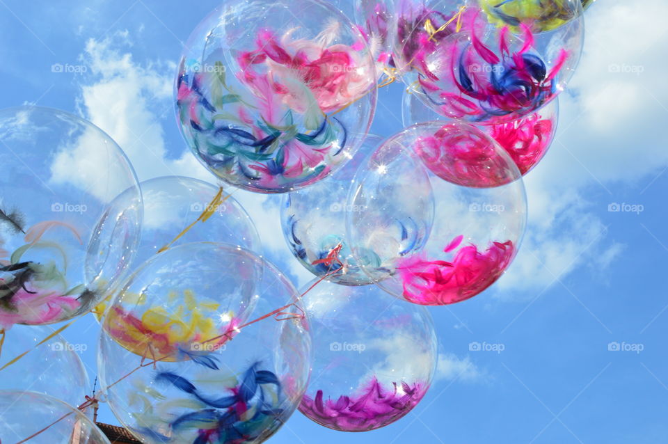 transparent balloons with colored feathers