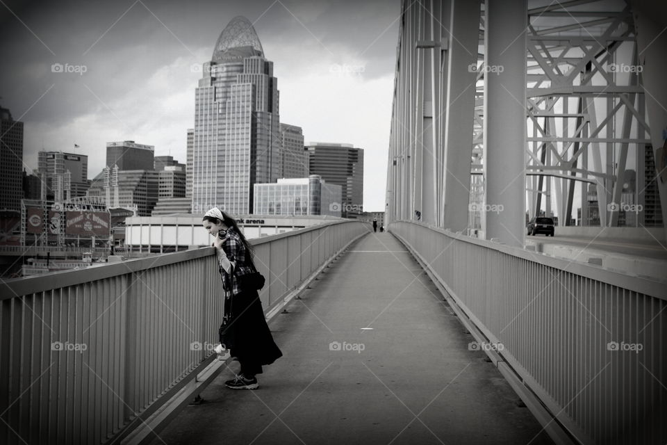 A black and white photo of a walk way beside a bridge going over the Ohio River with a girl looking over the rail.