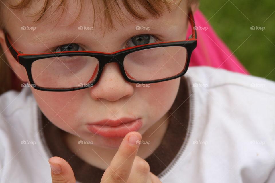 Portrait of little sad boy in eyeglasses