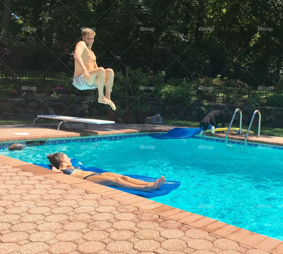 Young jumping into swimming pool