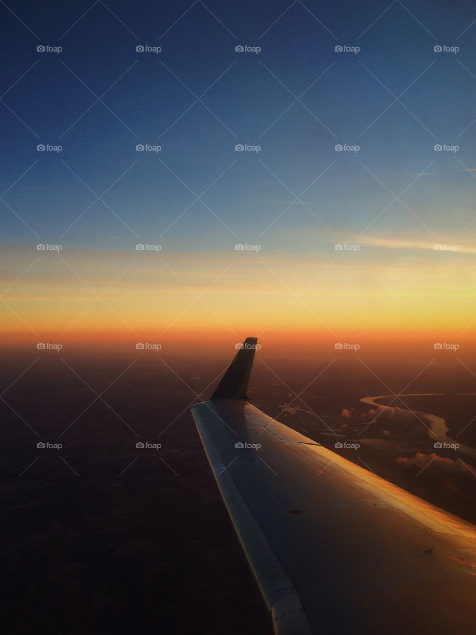 Airplane wing with sunset over Ohio River. Flying into the sunset over the Ohio River Valley