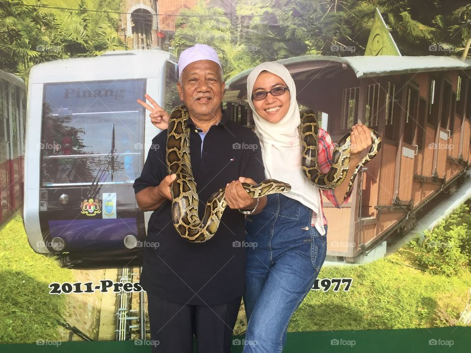 Portrait of father and daughter holding snake