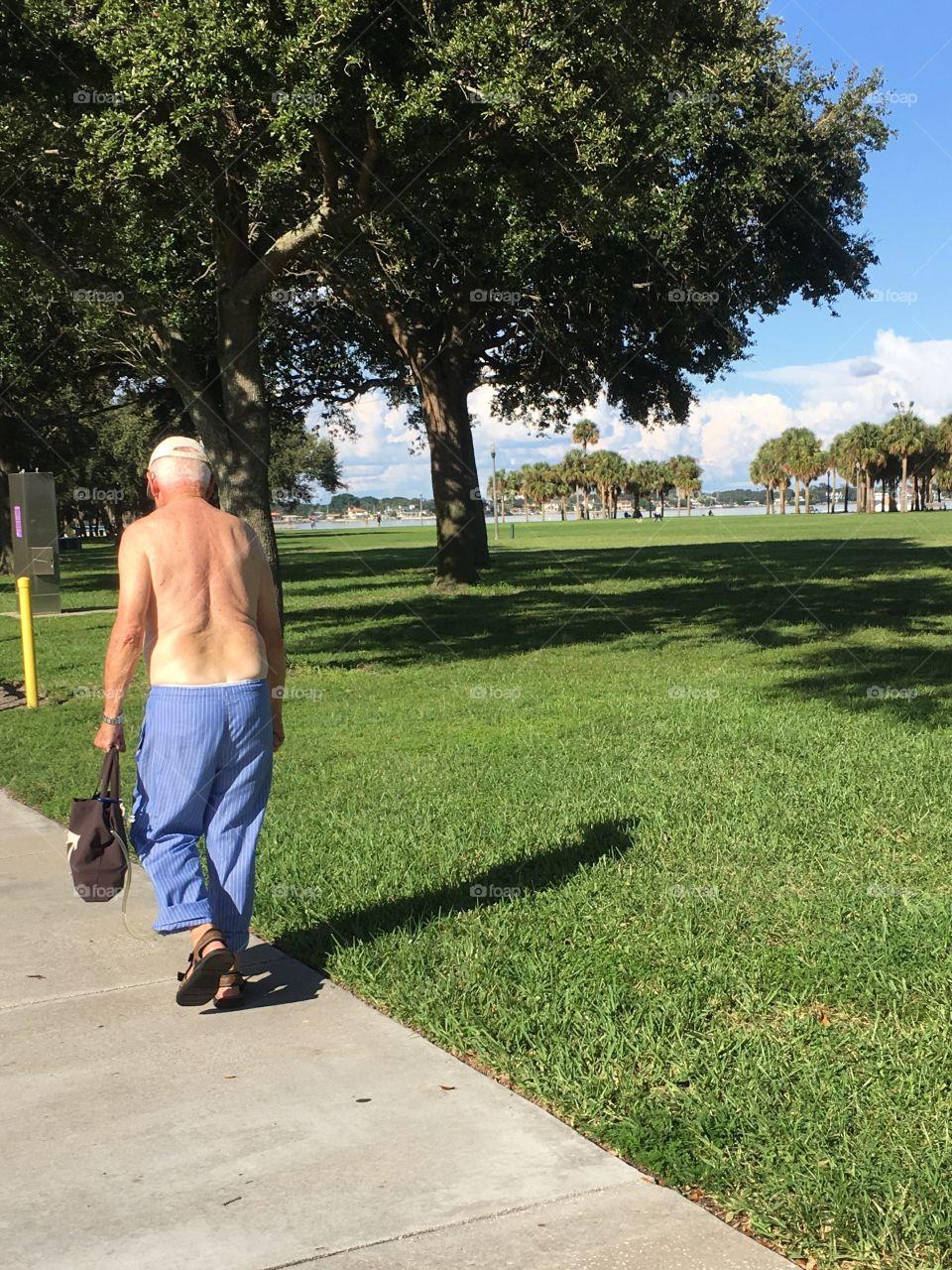 Topless grandpa with pj bottoms taking a walk