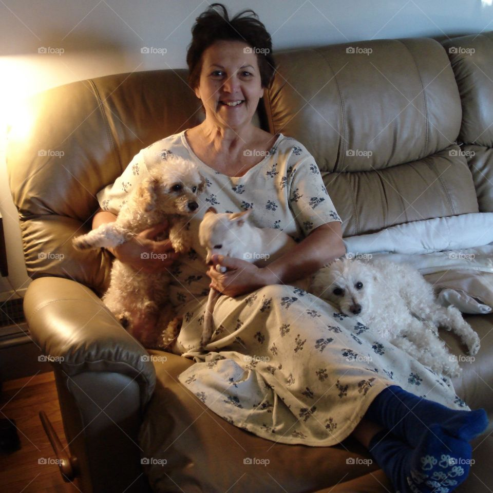 Mature woman with puppies sitting on sofa
