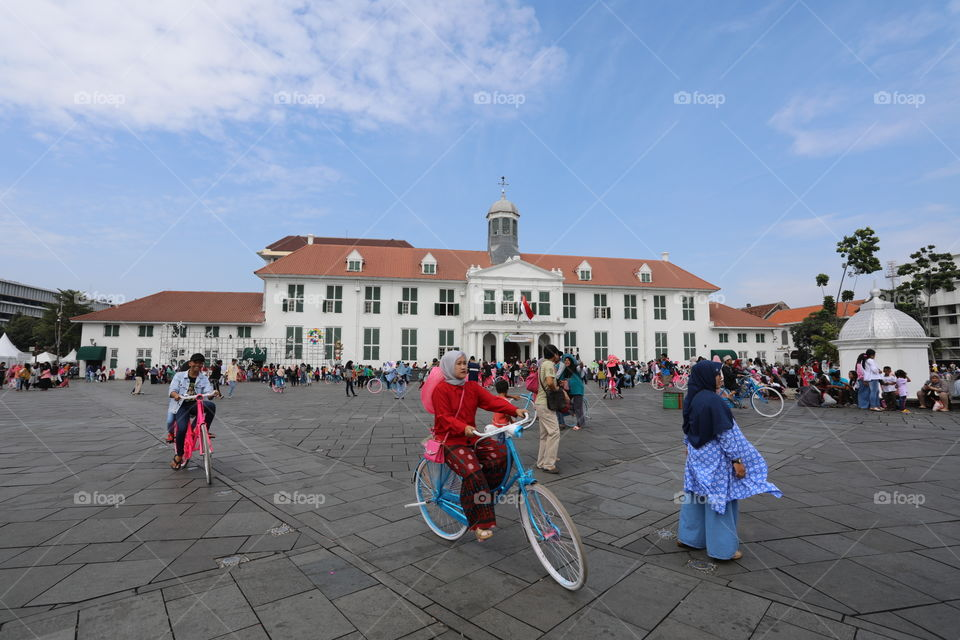 Locals cycle and walk through Fatahillah Square, with Jakarta History Museum in the background, in the Old Town of Jakarta, Indonesia