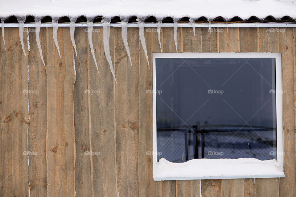 Icicles on the roof of a wooden house on a snowy winter day