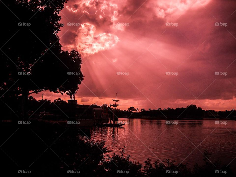 Dramatic sky over lake with silhouetted trees