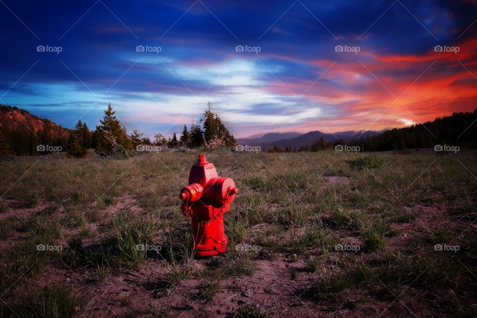 Water hydrant on hill at sunset