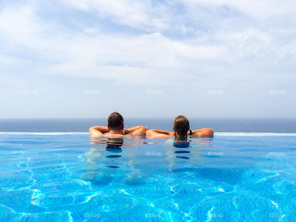 Rear view of couple in infinity pool