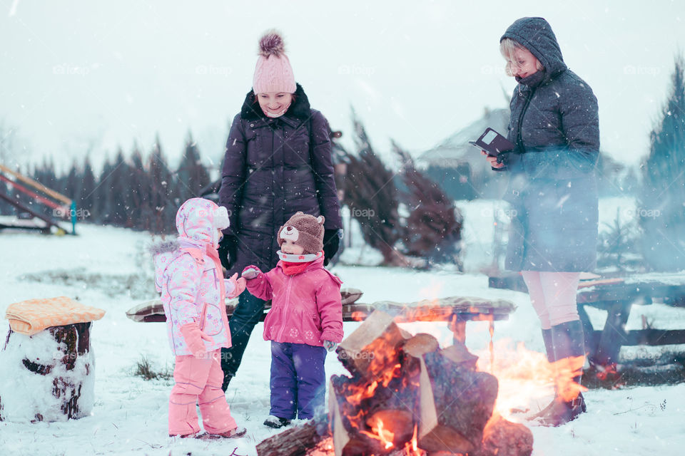 Family spending time together outdoors in the winter. Parents with children gathered around the campfire preparing marshmallows and snacks to toasting over the campfire using wooden sticks
