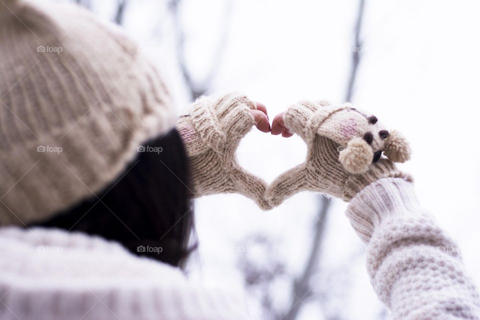 Woman shows a heart symbol with her fingers