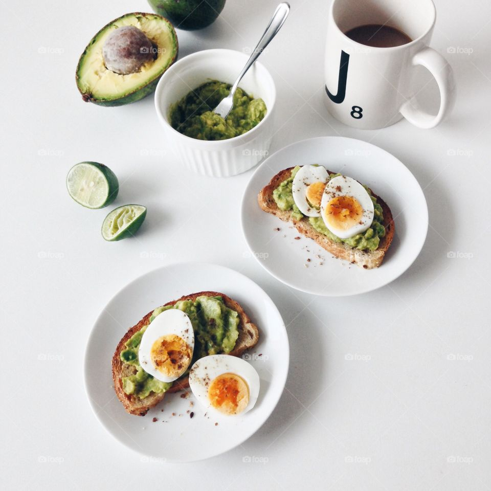 Healthy breakfast with avocado toasts and boiled eggs.