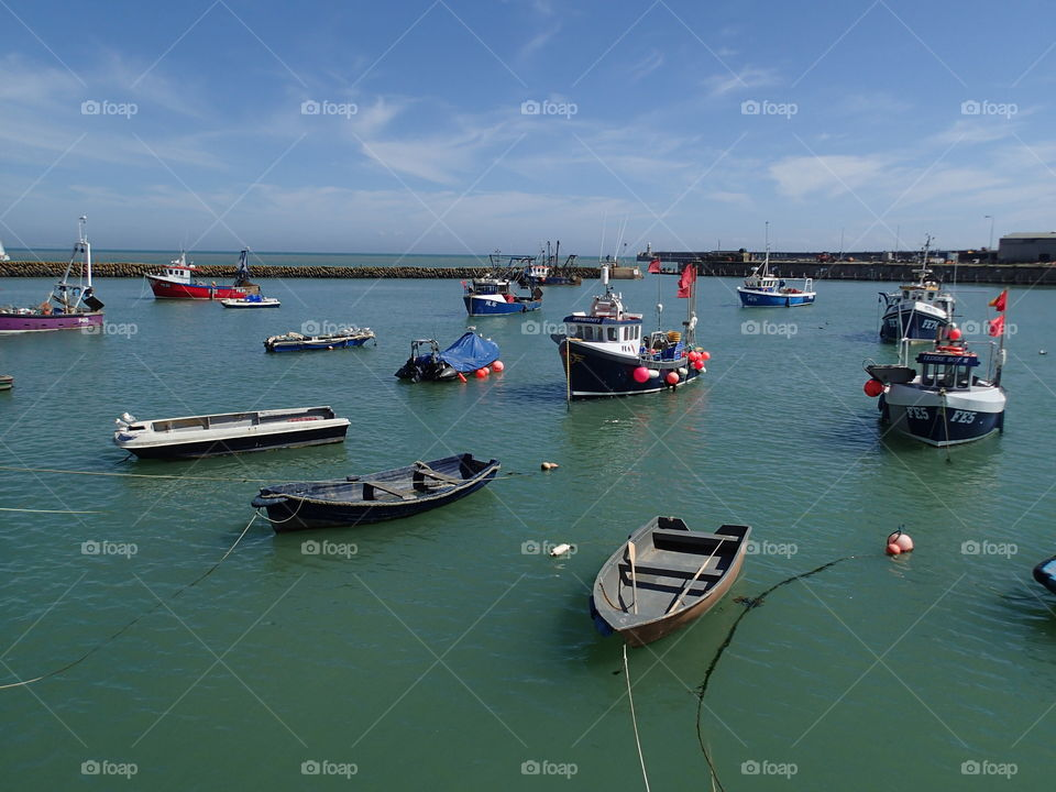 Fishing boats tied up or anchored in the calm harbor in Folkestone England on a sunny summer day.