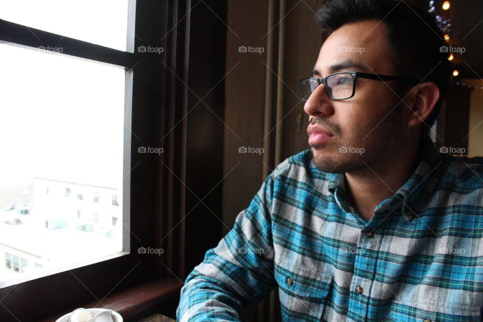Profile closeup portrait of a young Hispanic man pensively stares out the window in a dark room