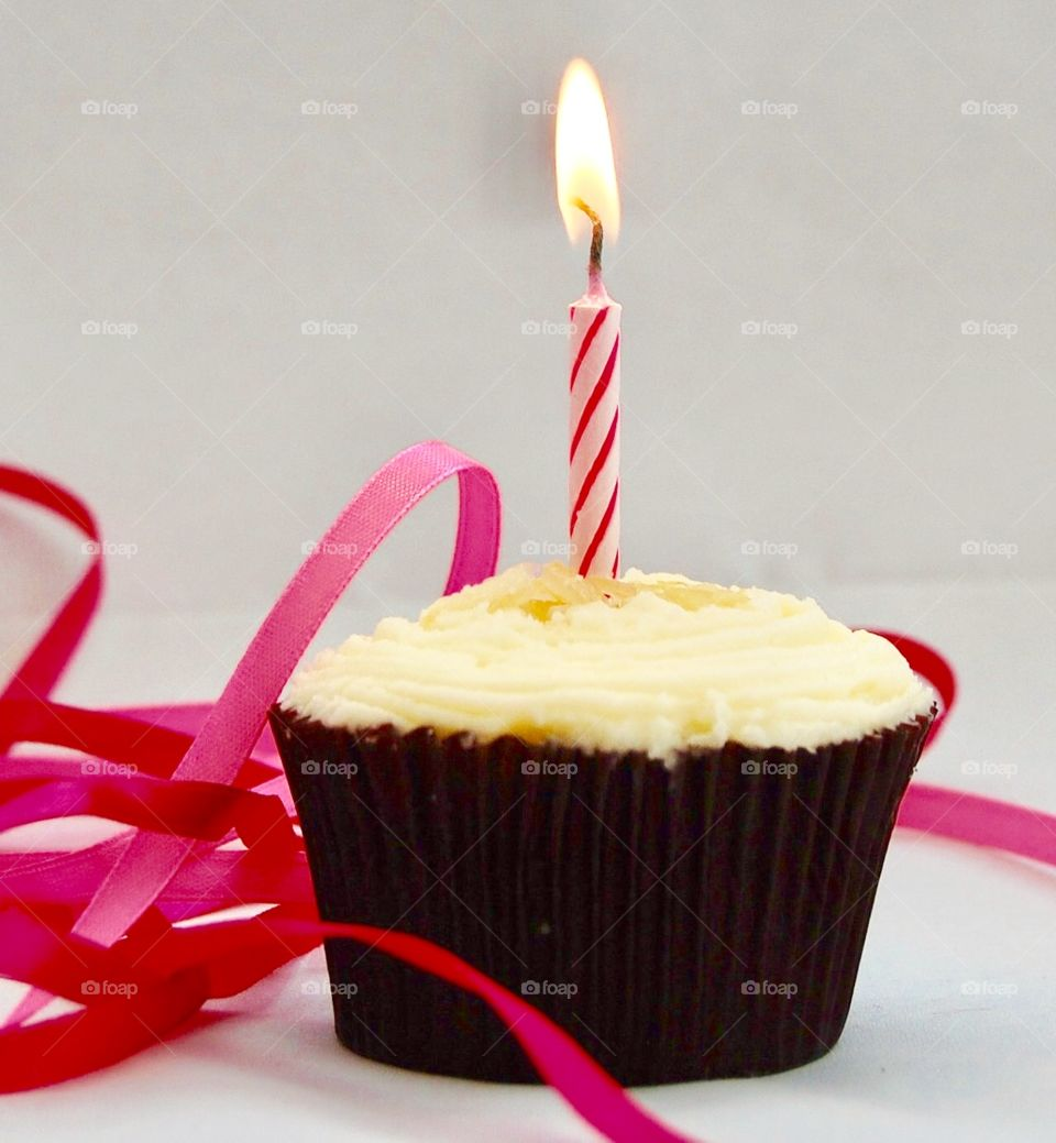 Single cupcake with pink lit candle and vanilla icing as a birthday cake with pink ribbons