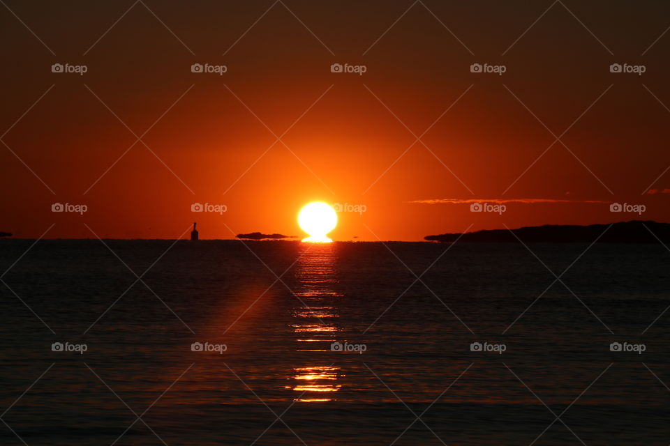 Sun rises above the horizon mirroring itself into the ocean... sky red and no clouds on this winter morning