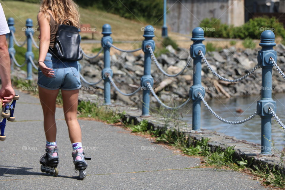 Young woman on skates carrying backpack overpasses a young man walking carrying a skateboard