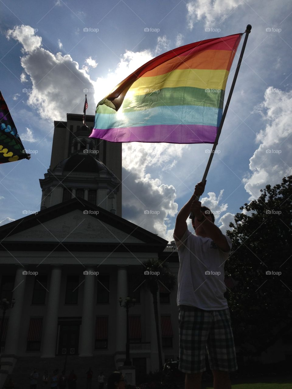 An activist waives a Pride flag in front of the historic Florida Capitol.