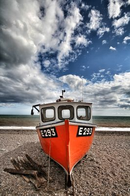 A beached fishing boat on a deserted pebble beach near the ocean.