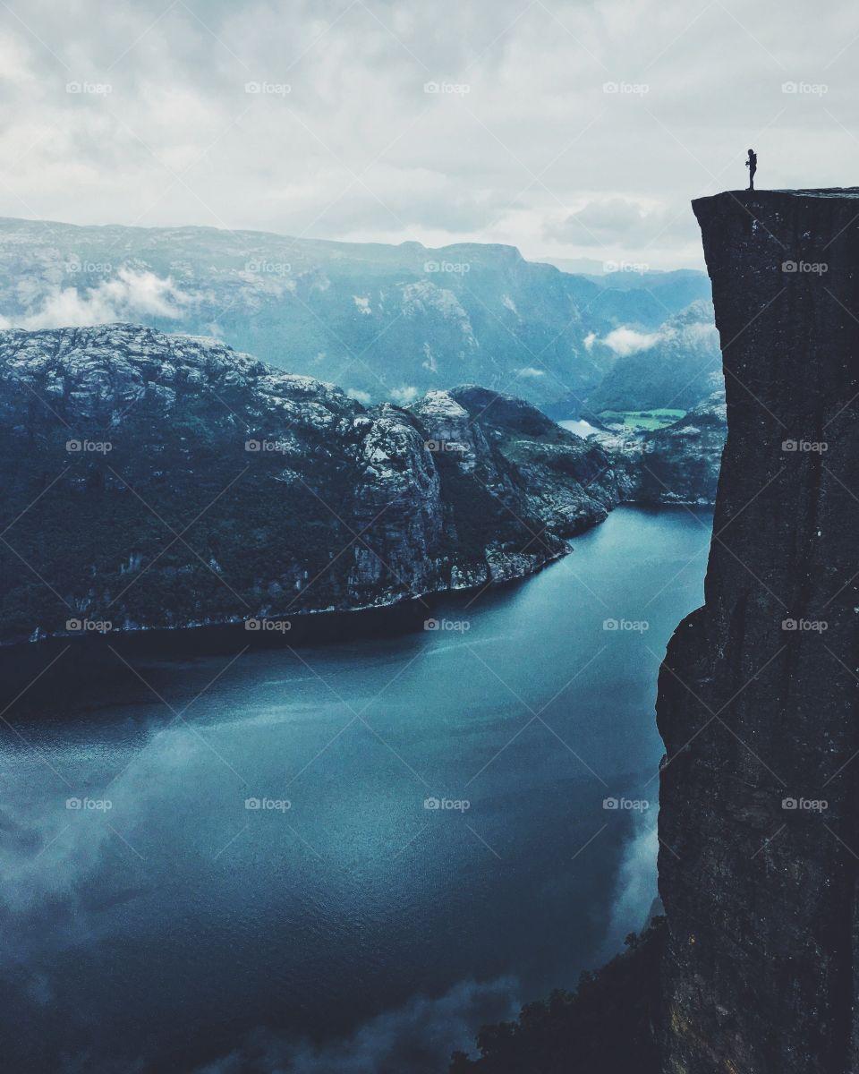 Tiny human standing on the edge of Prekestolen rock in Norway.