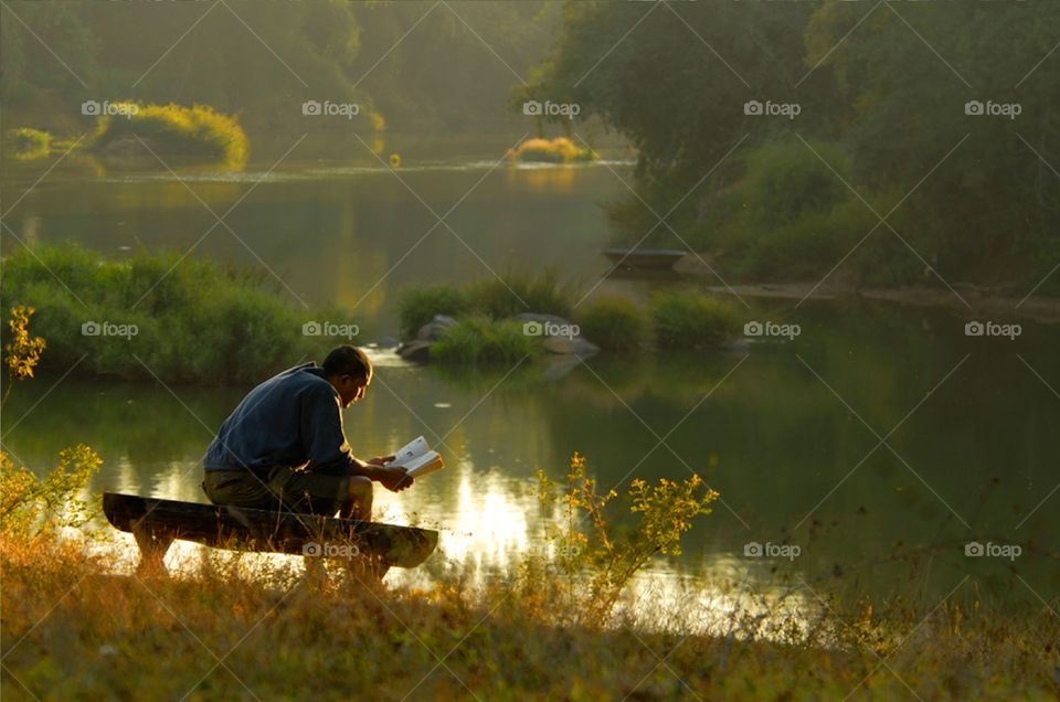 Young man relaxing & reading books alone enjoying his leisure in early winter afternoon