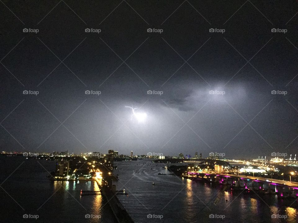 View of illuminated city during storm clouds