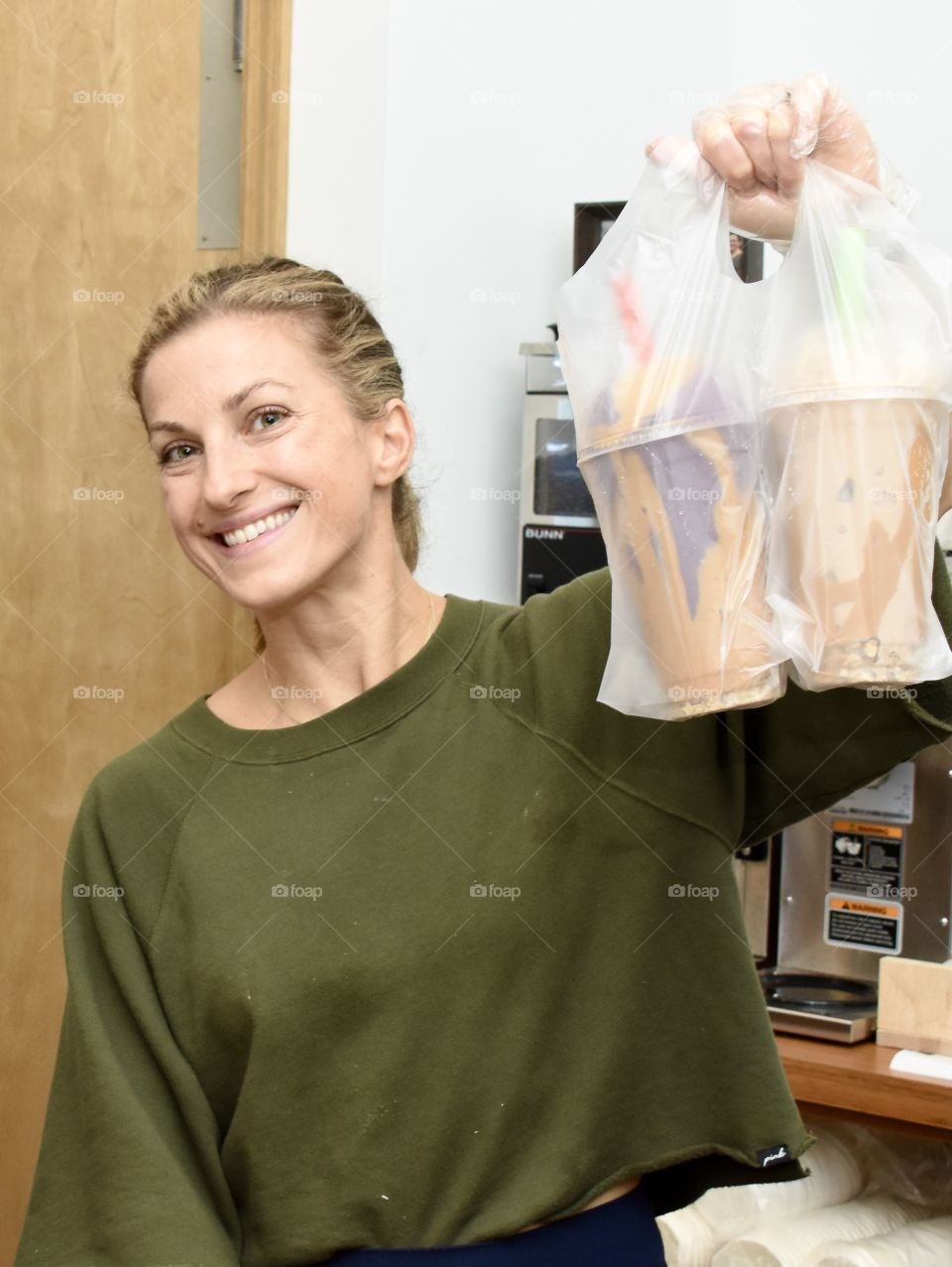 A woman who loves her job holding up smoothies