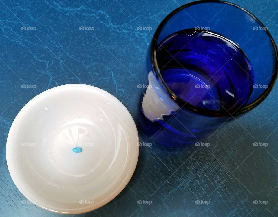 Medication time. Blue glass of water next to white dish with little blue pill in center.