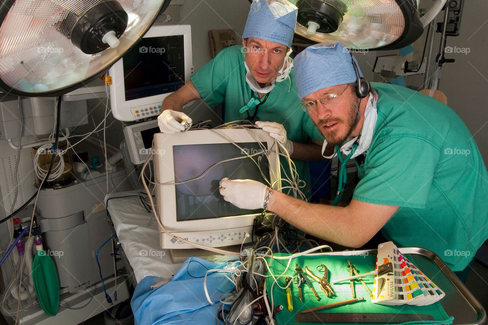 Two men operate on a computer in the emergency room at a hospital