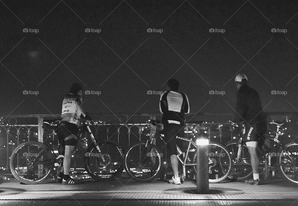3 cyclists admiring the view from top of the bridge