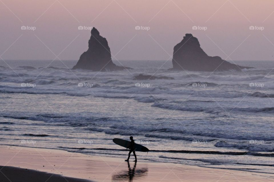 Lone surfer walking on beach during a sunset