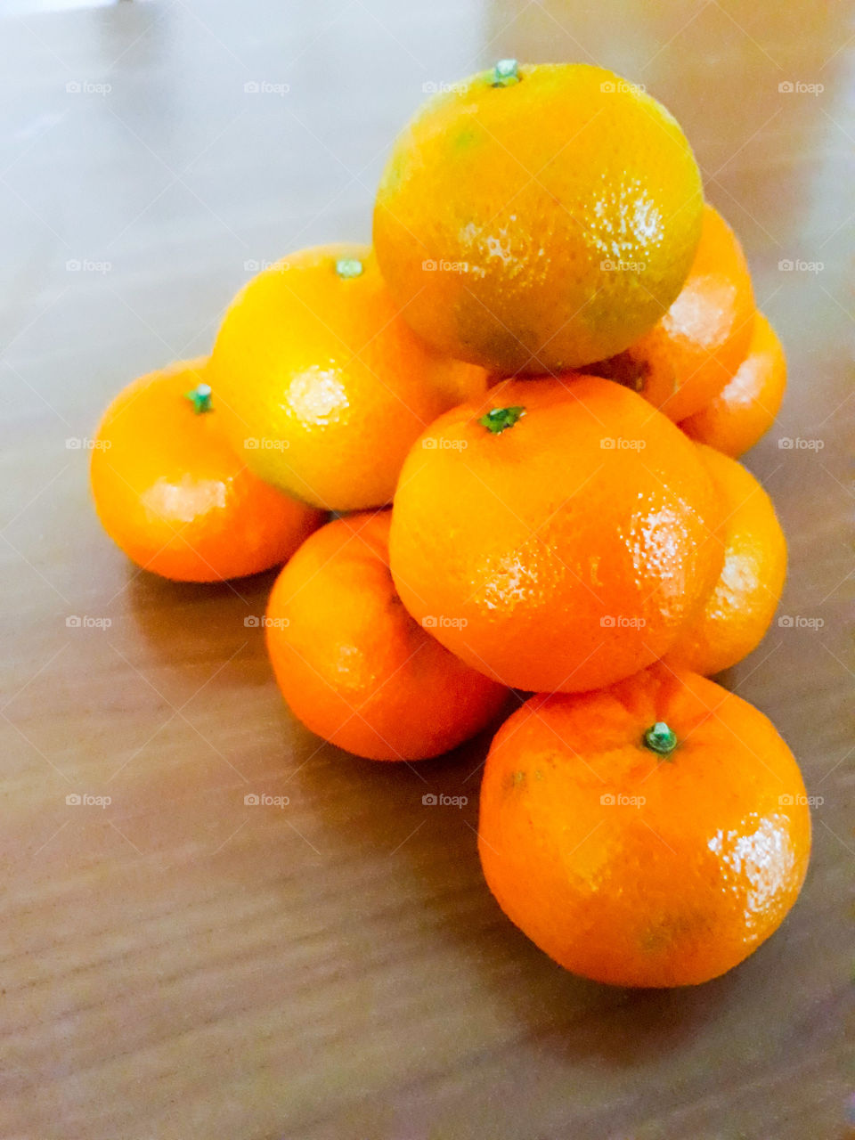 Pyramid of brilliant orange tangerines on a wooden background