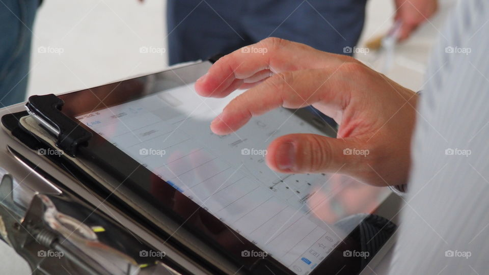 Man working with plans on ipad. Architect discussing architectural plans using his mobile tablet. Drawings review and proposals