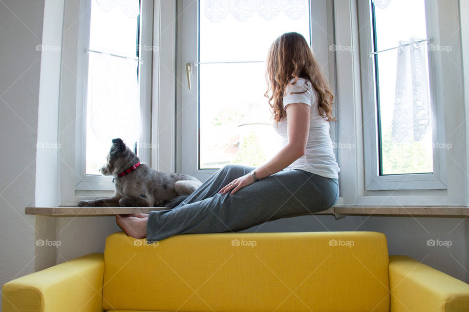 Woman and dog looking out window
