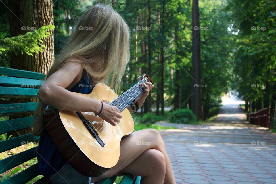 Girl learning to play guitar in a public park