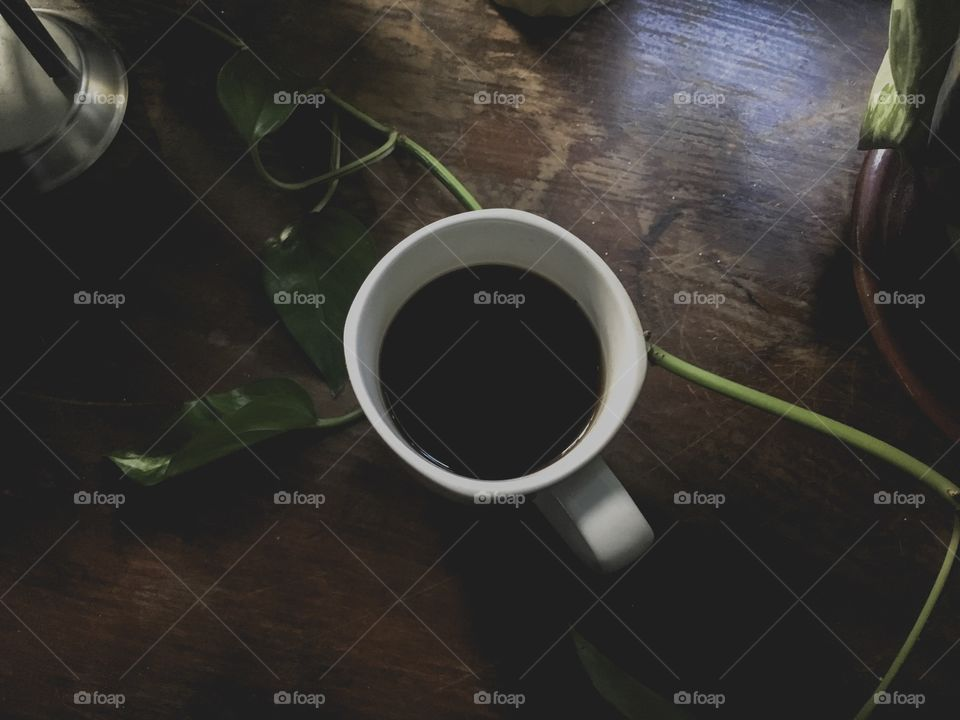 Dark black coffee in a white mug on a dark brown wooden table at a coffee shop, next to green leaves of an indoor plant