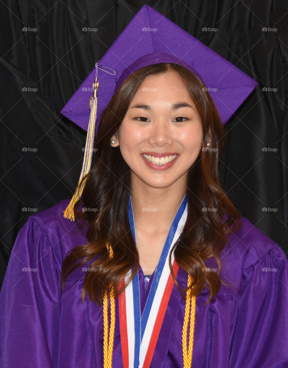 Graduating girl with purple cap and gown and honor cords