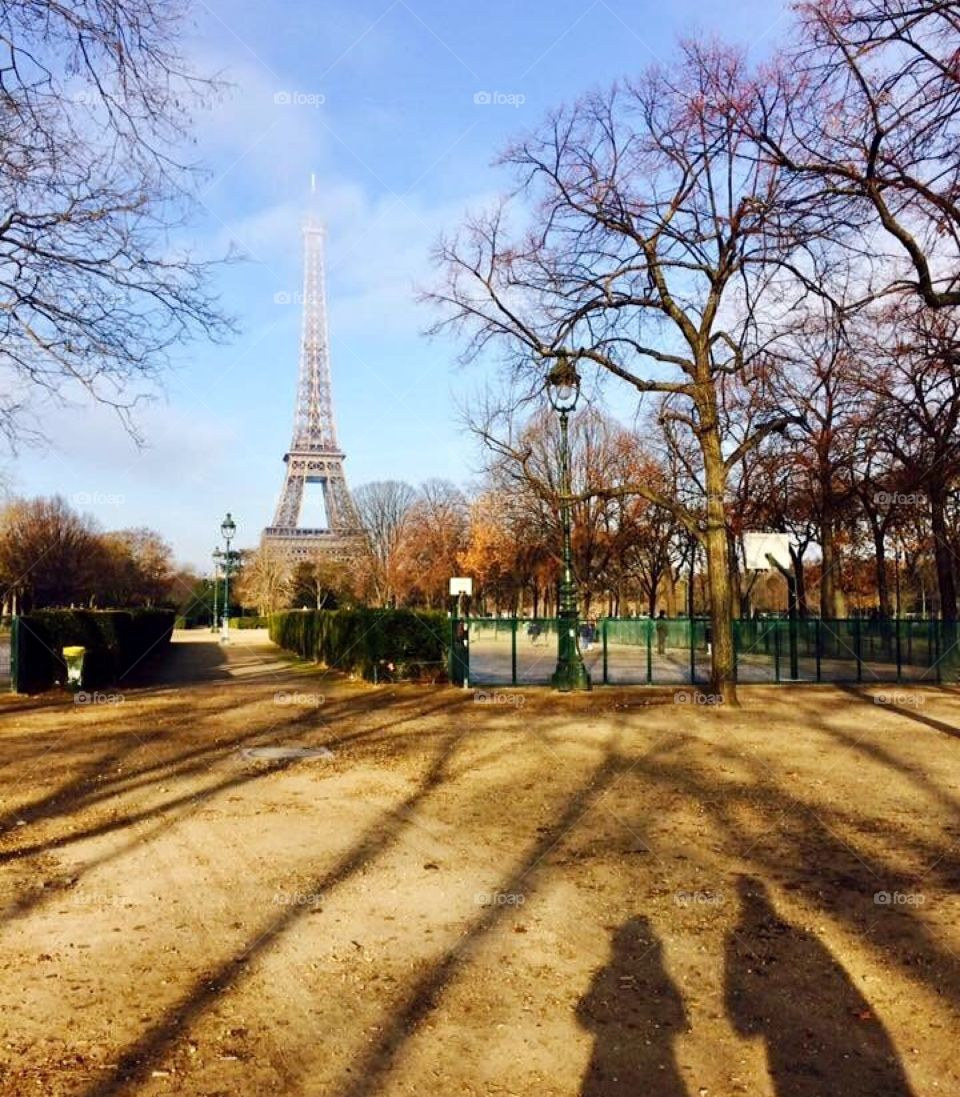 A beautiful picture in Paris of the Eiffel Tower in the distance and two shadows in the foreground
