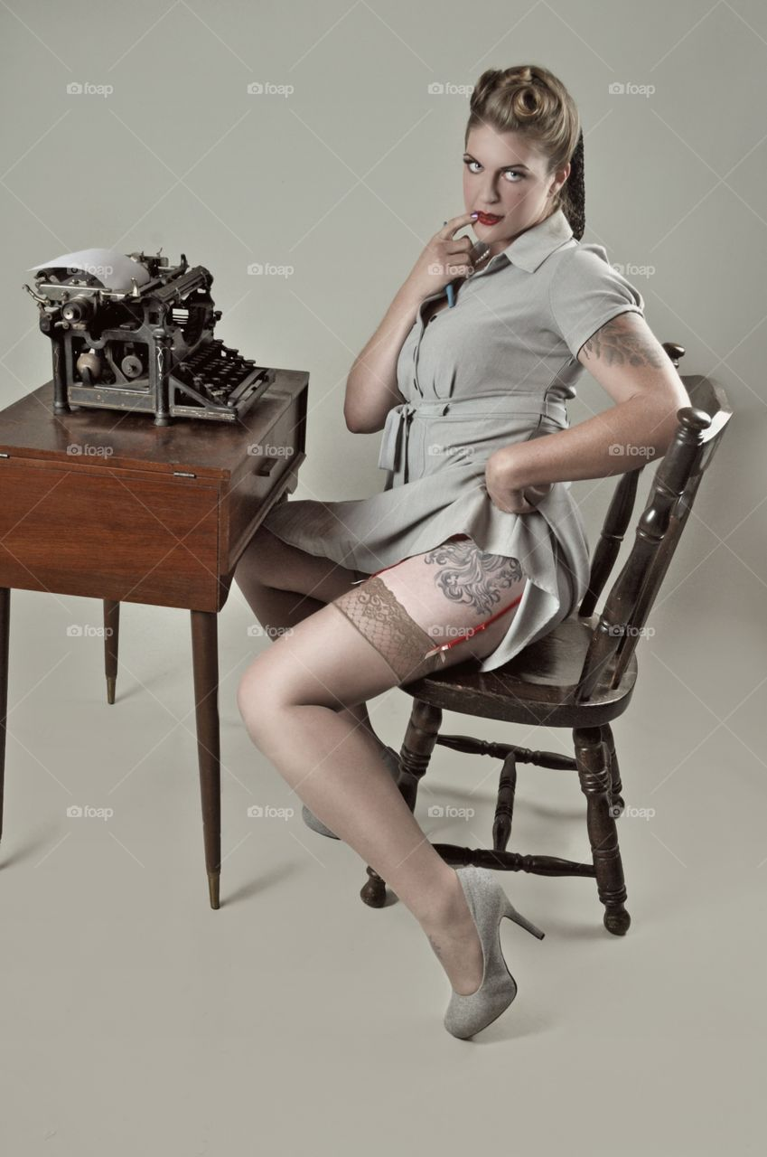 Woman showing her tattoo while sitting on wooden chair