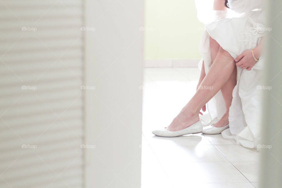 Low section view of bride wearing shoes