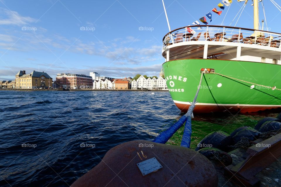 Stavanger harbor, Norway. Boat anchored at the harbor in Stavanger. View of the city in the background.