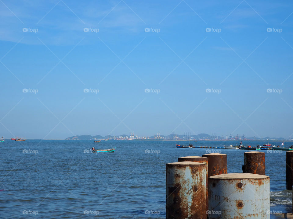 Harbor or pier with rusty metal pole and fishing boats and major seaport at the distant view.