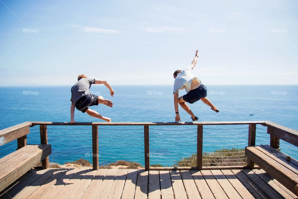 Two people jumping off boardwalk