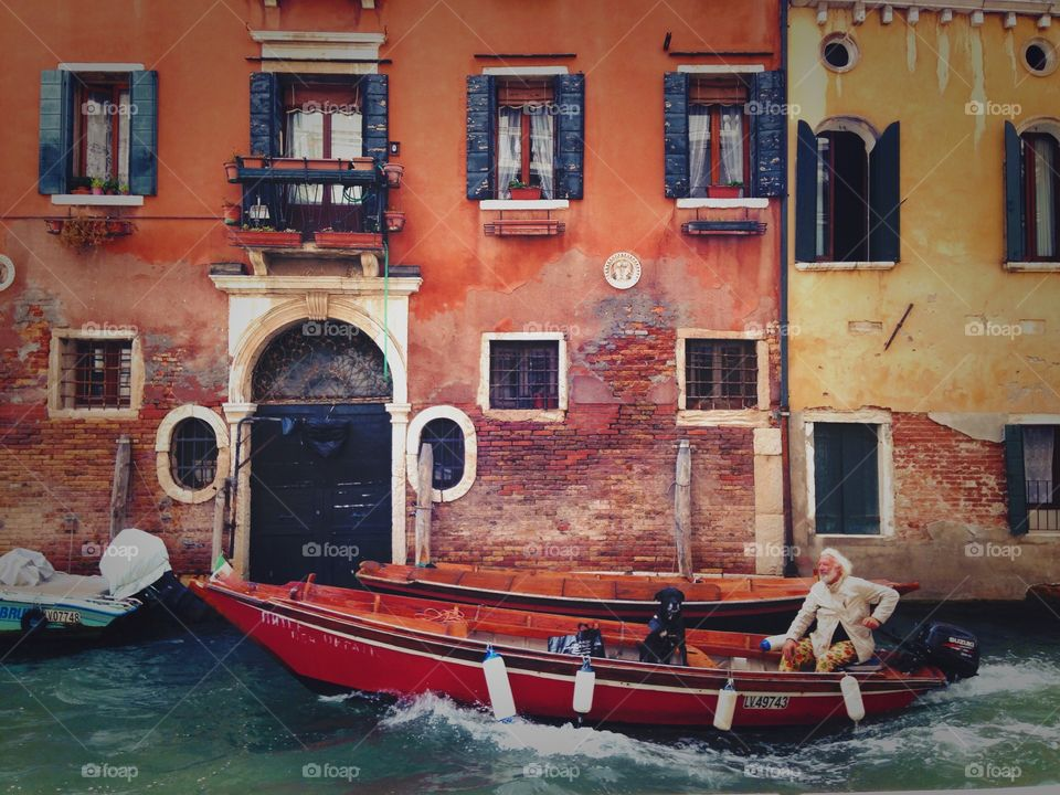 Beautiful grey haired elder man swimming in gondola with his dog-friend, enjoying the view and architecture in Venice.