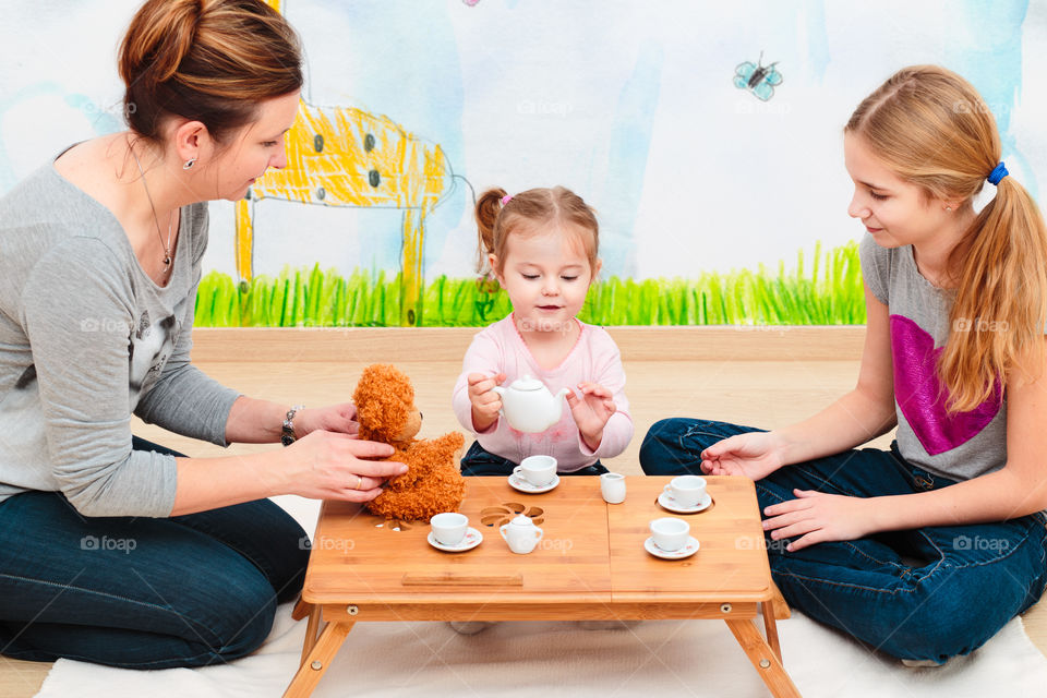 Little girl playing with mother and sister
