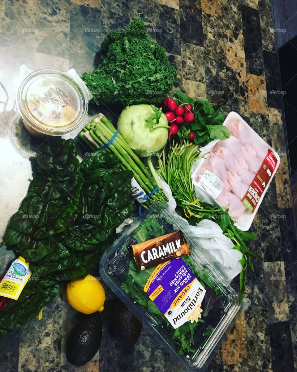A pile of many groceries, mainly vegetables is spread on a counter. On top of a spring mix is a Caramilk chocolate bar